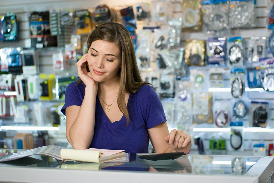 Young white female entrepreneur running a small business and working in a computer shop and checking bills and invoice with calculator doing budget and reviewing expenses.