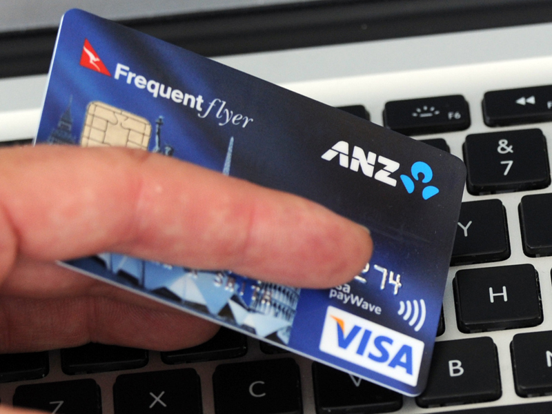 A credit card is held in front an online shopping site in Melbourne, Friday, Sept. 20, 2013. (AAP Image/Julian Smith) NO ARCHIVING