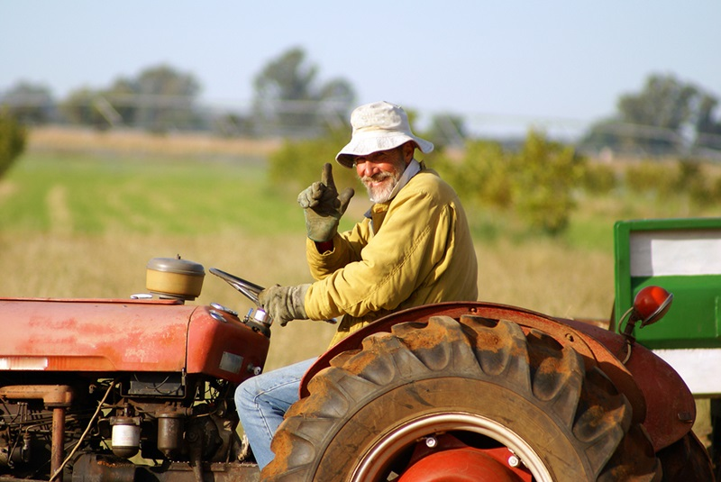 Happy farmer waving from his old red tractor. Clearly he is very happy being a farmer.