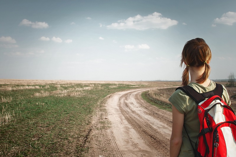 Young woman with backpack on rural road looking to somewhere