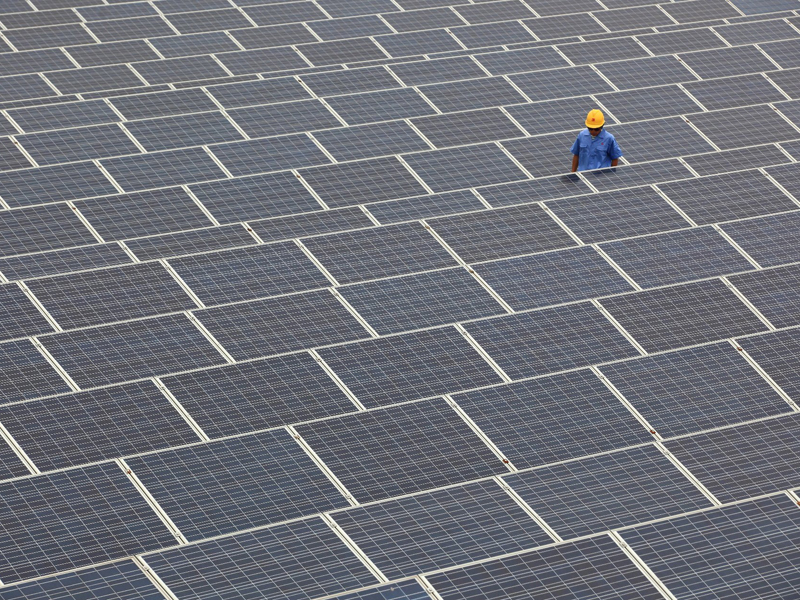 --FILE--A Chinese electrician checks the operation of solar panels at a rooftop photovoltaic (PV) power station at the plant of Qingdao Jifa Group in Qingdao city, east Chinas Shandong province, 26 June 2013. China aims to more than quadruple solar power generating capacity to 35 gigawatts by 2015 in an apparent bid to ease a massive glut in the domestic solar panel industry. The target has been stated previously by the State Grid, which manages the countrys electricity distribution, but now has the official backing of the State Council, the countrys cabinet and its top governing body. China will add around 10 gigawatts per year from 2013-2015, the State Council said in a statement.